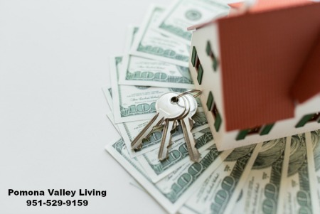 Small house sitting on money with keys