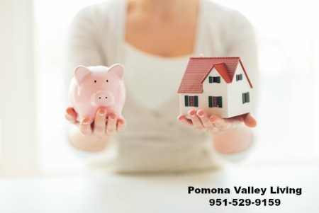 woman holding bank and small house